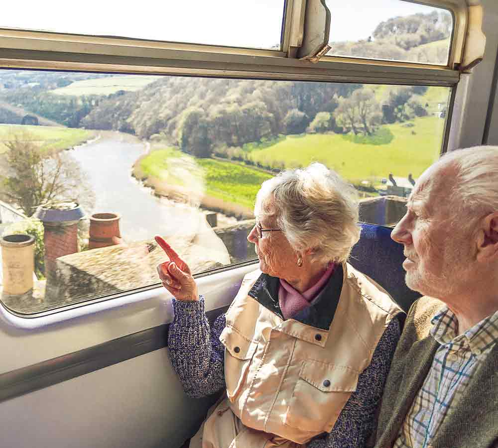 Couple looking out of the train window as train passes over Calstock Viaduct