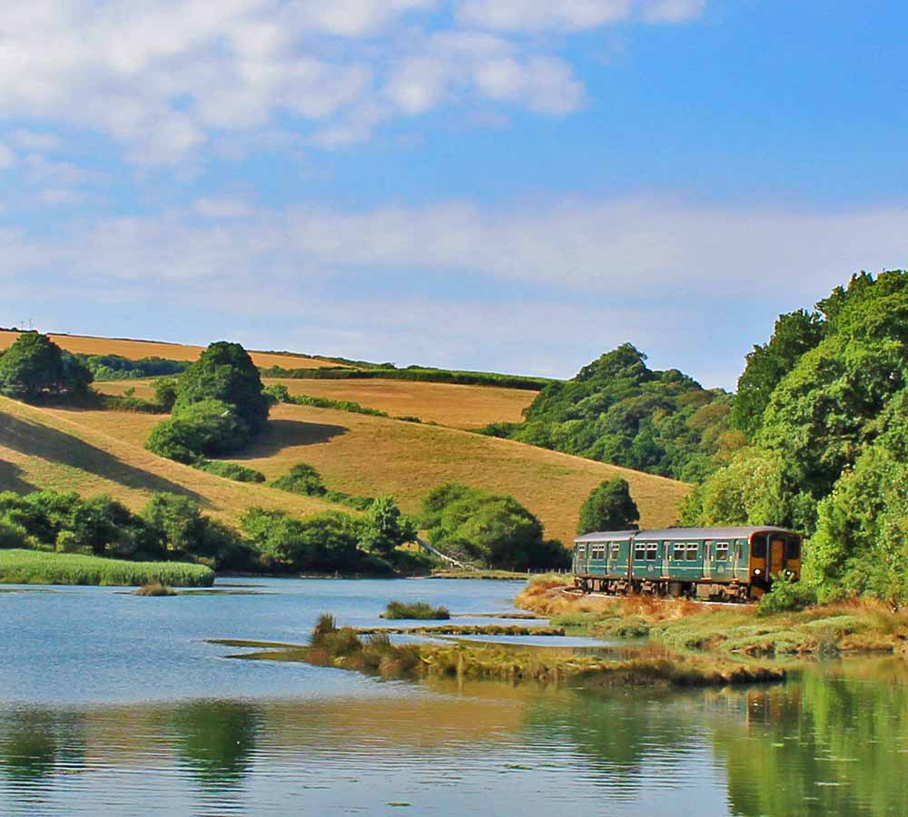 GWR train running alongside the estuary on the Looe Valley Line