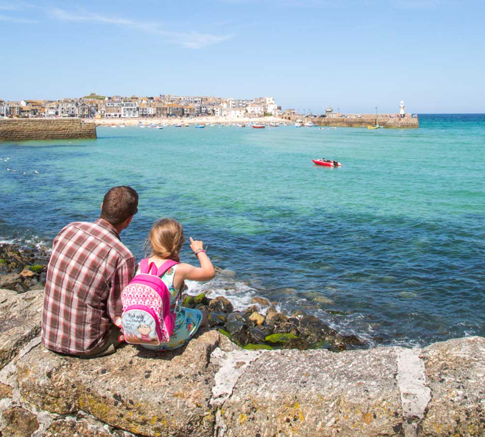 Father and daughter look across water to St Ives