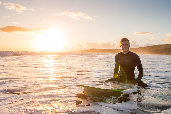 Young man on a surfboard in the sea