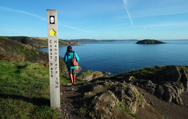 Walker on the coast path from Looe next to coast path sign post