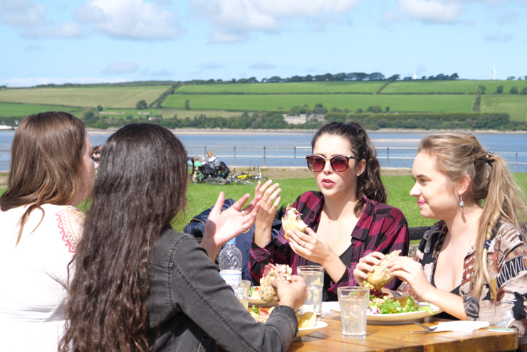 Friends eating lunch outside the Fremington Quay Cafe on the Tarka Trail from Barnstaple