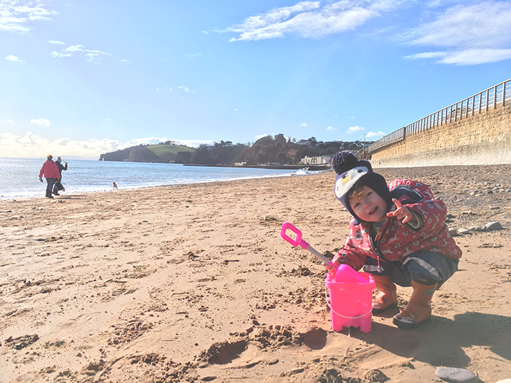 Toddler on Dawlish beach with bucket and spade