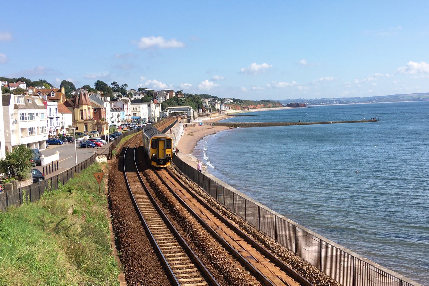 Train departing Dawlish station for Teignmouth with sea to the right