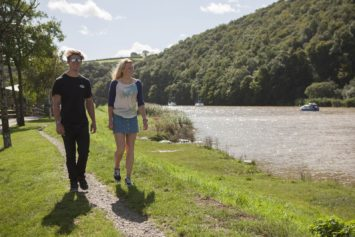 Young man and woman walking in sunshine at Calstock