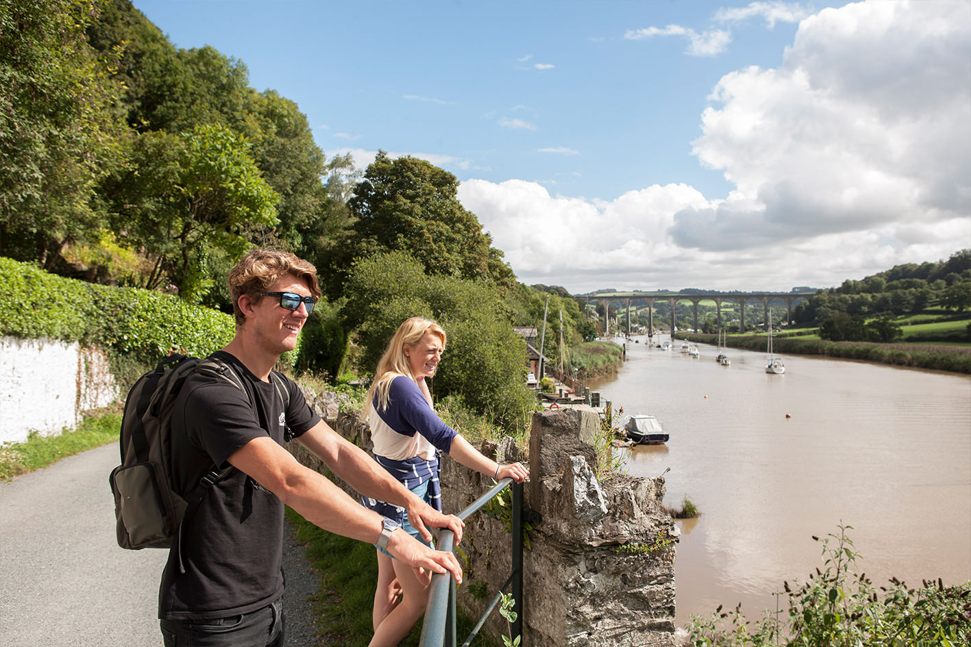 Young couple on the walk from Calstock to Cotehele National Trust with Calstock Viaduct in background