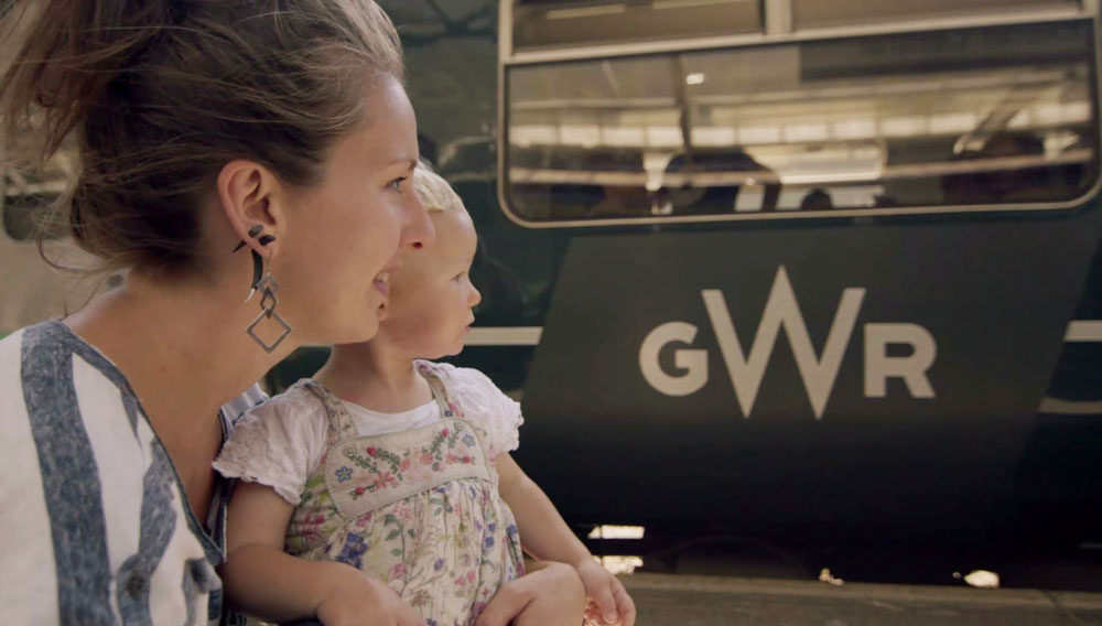 Family looking at GWR train as it approaches