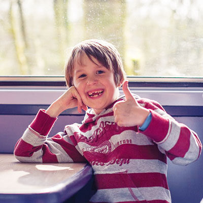 Boy with thumbs up on train